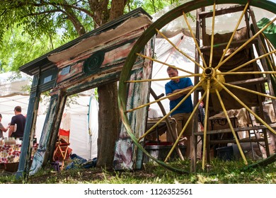 Braselton, GA / USA - April 28, 2018:  People look at antique fireplace mantels and wagon wheels on sale at the Braselton Antique Festival on April 28, 2018 in Braselton, GA.