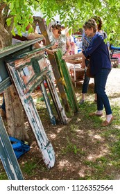 Braselton, GA / USA - April 28, 2018:  A woman looks at an antique wagon wheel and old fireplace mantel pieces on sale at the Braselton Antique Festival on April 28, 2018 in Braselton, GA.