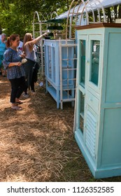 Braselton, GA / USA - April 28, 2018:  Women shop and look at antique cabinets for sale at the Braselton Antique Festival on April 28, 2018 in Braselton, GA.