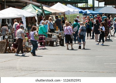 Braselton, GA / USA - April 28, 2018:  A large group of people walk and look at antiques on sale at the Braselton Antique Festival on April 28, 2018 in Braselton, GA.