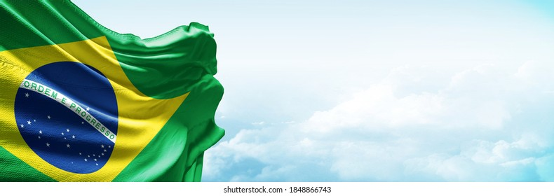Brasil flag in the blue sky. Horizontal panoramic banner.