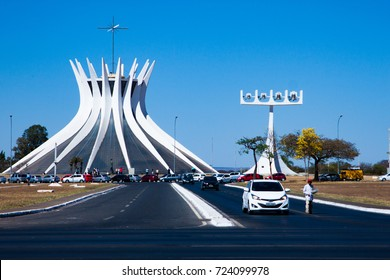 """Brasilia, Brazil. August 2017. The Cathedral of Brasilia: """"Metropolitan Cathedral of Our Lady of Aparecida"""". Street view with incidental persons."""