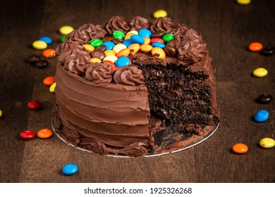 Brasilia, Brazil - February 11, 2021: Sliced mms chocolate cake with scattered mms around on a wooden table.