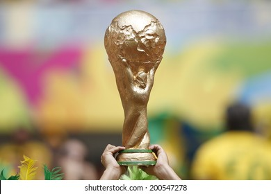 BRASILIA, BRAZIL - JUNE 23, 2014: A fan showing a fake World Cup Trophy during the World Cup Group A game between Cameroon and Brazil in the National Stadium. NO USE IN BRAZIL.