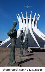 """Brasilia, Brazil - june 9 2018. View of bronze statues in front of The Cathedral of Brasilia: """"Metropolitan Cathedral of Our Lady of Aparecida""""."""