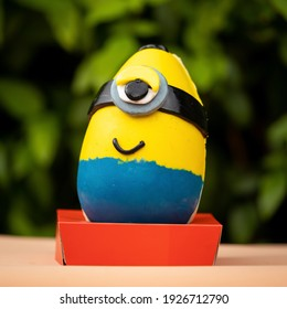 Brasilia, Brazil - March 19, 2020: Minion easter egg on a red stand in a green nature background.