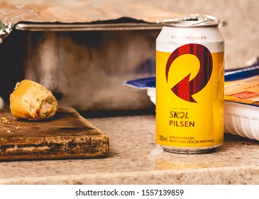 Brasilia, Federal District - Brazil. Circa, 2019. Photograph of a Skol beer can in barbecue setting with garlic bread left in the image.
