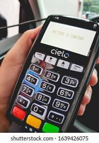 Brasilia, Federal District - Brazil. Circa, February, 2020. Man holding Cielo company credit and debit card machine.