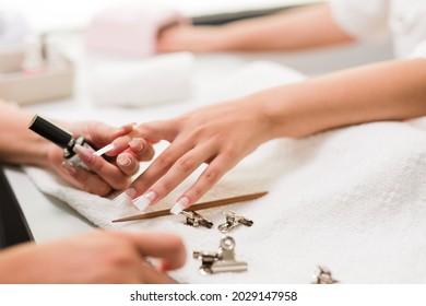 Brasilian latin mid woman manicure profesional puting to a client fiberflass nails autumn evoque