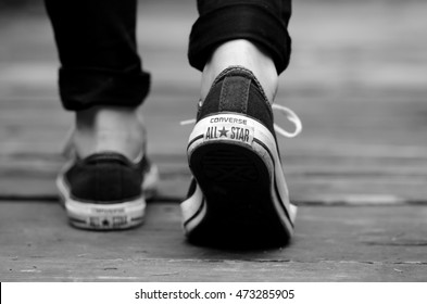 Brasov, 22.08.2016: Converse All Star shoes for girls on foot while walking on wood, b&w
