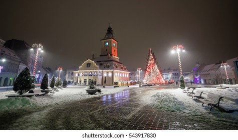 Brasov Council House night view with Christmas Tree decorated and traditional winter market in the old town center, Romania