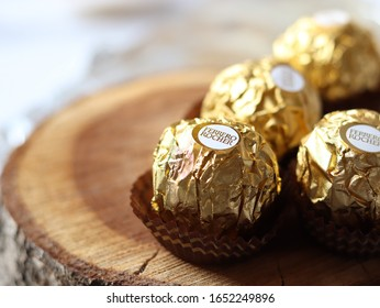 Brasov, Romania - 2/22/2020: 4 pieces of Ferrero Rocher chocolate on a wood background, luxury concept, the perfect gift, Italian sweets