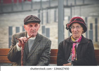 Brasov, Romania - 5/1/2016: Old pensive people couple man and woman sitting on a bench