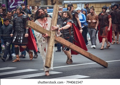Brasov, Romania - April 14, 2017: Actor plays wounded tired Jesus Christ carrying large wooden cross during the reenactment of the Stations of the Cross on Good Friday.