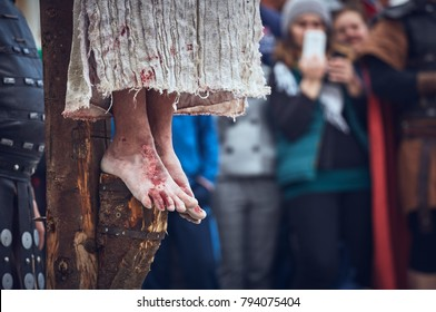Brasov, Romania - April 14, 2017: Detail with nailed bleeding feet of Jesus Christ crucified during the street reenactment of the Stations of the Cross on Good Friday.