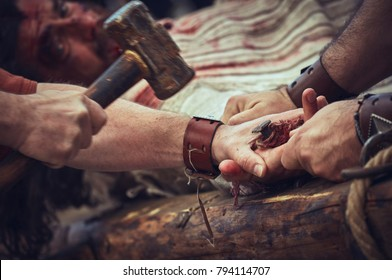 Brasov, Romania - April 14, 2017: Actor playing Jesus Christ is getting his hands nailed while being crucified during the reenactment of the Way of the Cross on Good Friday.