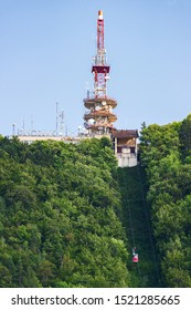 BRASOV, ROMANIA - AUGUST 17, 2019: Television relay on Tampa peak from above. Funicular rises to the top. Sunny day