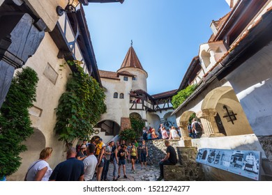 BRASOV, ROMANIA - AUGUST 18, 2019: Bran Castle yard and balcony with walking people in sunlight. Top view from a red roof