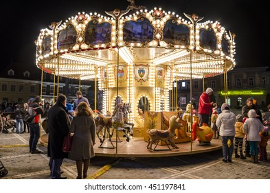BRASOV, ROMANIA - CIRCA DECEMBER, 2015 - Unidentified people guide small children in using the carousel, with little ponies and glowing lights