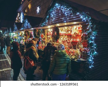 Brasov, Romania - December 2, 2018: Tourists come at the Christmas fair in the Council Square and visit the decorated stands to buy traditional souvenirs, sweets and all kinds of home made goods.