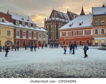 Brasov, Romania - January 20, 2019: Group of tourists visit the snowy Council Square and the Black Church, a Gothic style monument and one of the most important Lutheran worship places in the region.