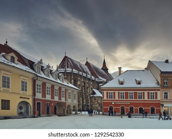 Brasov, Romania - January 20, 2019: Dark storm clouds over the snowy Council Square and the Black Church, a Gothic style monument and one of the most important Lutheran worship places in the region.