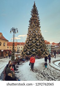Brasov, Romania - January 20, 2019: Tourists relax near the tall festive traditional Christmas tree in the snowy Council Square of the medieval city during the winter holidays.