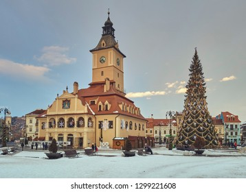 Brasov, Romania - January 20, 2019: Tourists visit the Brasov County Museum of History, the traditional Christmas tree and fair in the snowy Council Square in the historic center of the medieval city.