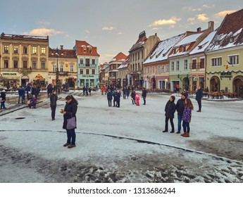 Brasov, Romania - January 20, 2019: Tourists enjoy the sites in the snowy Council Square in the historic center of the medieval city of Brasov, 7th largest and the most visited town in Romania.