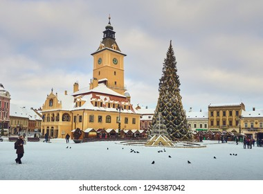 Brasov, Romania - January 8, 2019: Tourists visit the Brasov County Museum of History, the traditional Christmas tree and fair in the snowy Council Square in the historic center of the medieval city.
