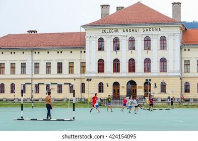 BRASOV, ROMANIA - JULY 26, 2015: Boys play football in the yard of a public school.
