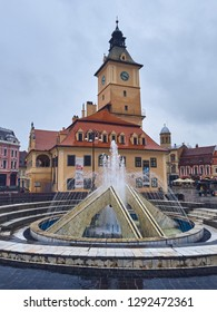 Brasov, Romania - July 9, 2018: Brasov County Museum of History building and artesian water fountain in the Council Square in the historic center of the old medieval city, on a rainy day.