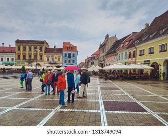 Brasov, Romania - July 9, 2018: Group of tourists with umbrellas enjoy a rainy city break in the Council Square in the historic center of the 7th largest and the most visited town in Romania.
