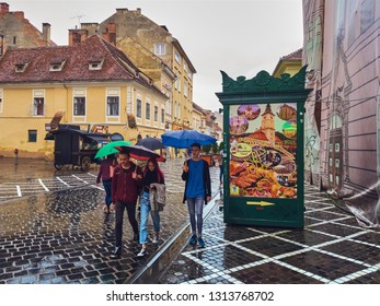 Brasov, Romania - July 9, 2018: Young people with umbrellas enjoy a walk on the wet cobblestone streets, on a rainy day, in the historic center of the 7th largest and the most visited town in Romania.