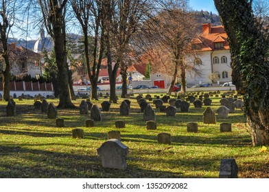Brasov, Romania,10 March 2019 - Cemetery of veteran soldiers with green grass and trees shadows on the ground.Sinister atmosphere in a cemetery