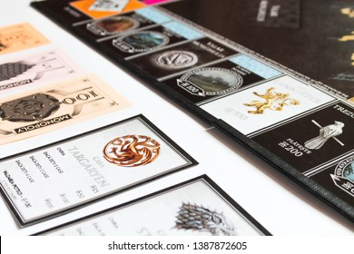 Brasov/Romania - 5/3/2019: Game of Thrones Edition Monopoly Board Game, Collector's Edition, Romanian version, flatlay, game board, cards, money isolated on white background, Targaryen House  in focus