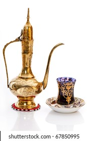 Brass Arabic coffee pot with a cup of coffee symbolising hospitality and welcoming a guest.