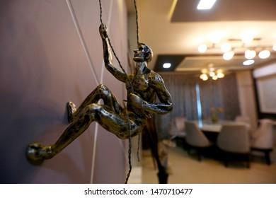 Brass artefact of climbing man statue