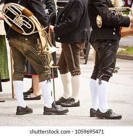 Brass band musicians in Bavarian costume attending a traditional parade