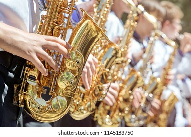 The brass band plays on the street in the city park at the festival. Closeup of a group of saxophonists.