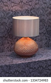 Brass bedside lamp. Copper lamp with lampshade, gold-colored fashionable lamp.