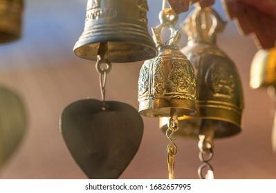 ฺSmall brass bells hanging on temple roof, close up shinning beautiful brass bells. Faith of Buddhism in Thailand. Soft warm Light beam in the air. Selected focus, blur background and foreground.
