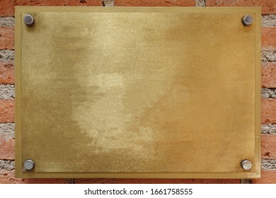 Brass or bronze metal plate on brick wall background. empty copy space for inscription.