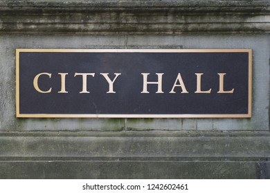 Brass City Hall sign on a stone wall