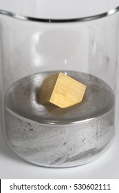 Brass cube floats in a beaker of mercury.