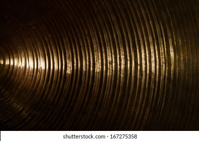 Brass cymbal texture with light shading on dark room.