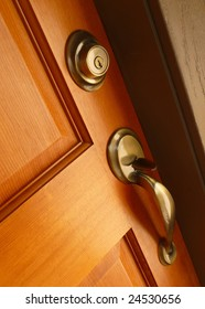 Brass door handle and deadbolt on wooden door