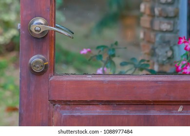 Brass door handle on the background of the green garden.Wooden Door Knocker and Glass Door.