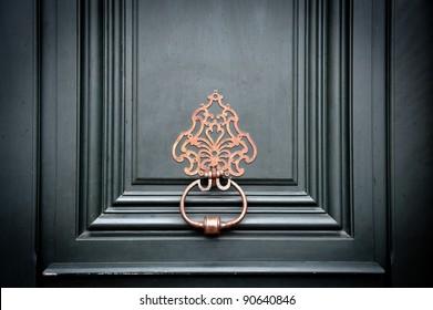 Brass door knocker on an entrance door in Paris