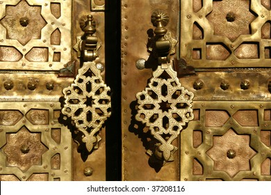Brass gate with doorknockers. On a house somewhere in medina of Marrakech, Morocco